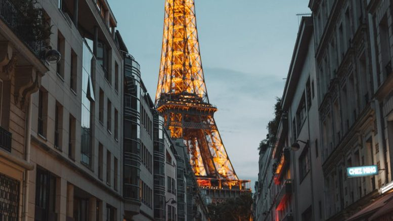 photo of cars parked on side of street across the eiffel tower