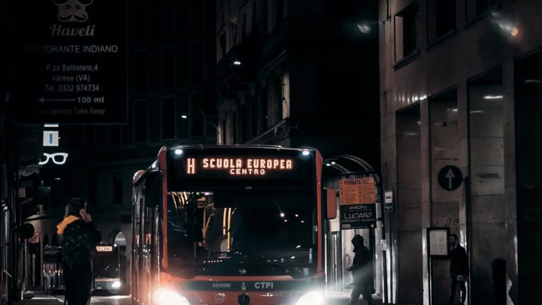 public bus driving along night street