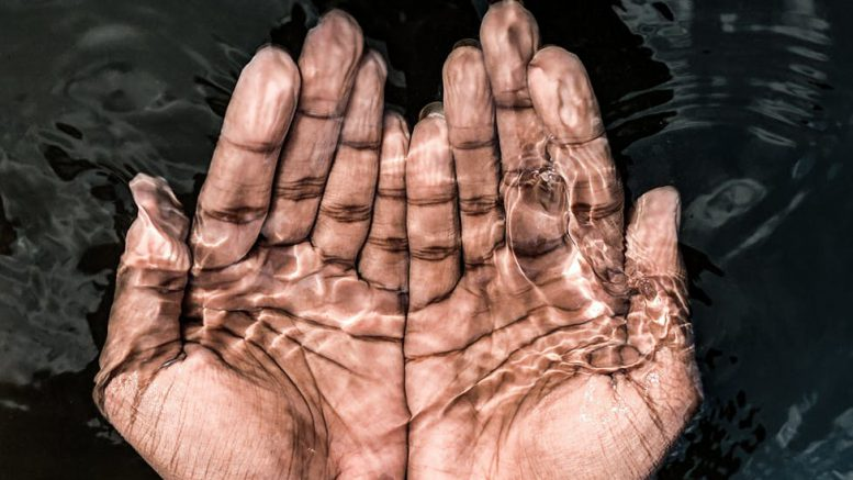 crop man with hands under transparent water