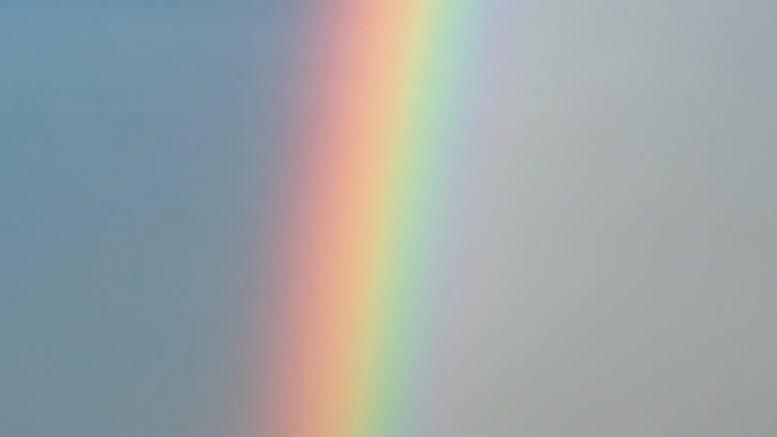 sky with rainbow over rippling blue ocean